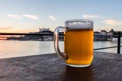 Koud glasmok bier met schuim op het kasteel en de rivier Donau achtergrond van Bratislava royalty-vrije stock afbeeldingen
