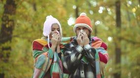 Koud griepseizoen, lopende neus Het tonen van zieken die coule bij de herfstpark niezen Jonge coule blazende neus bij aard stock videobeelden