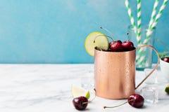 Koude de Muilezelscocktail van kersenmoskou met gemberbier, wodka, kalk Marmeren achtergrondexemplaarruimte Stock Fotografie
