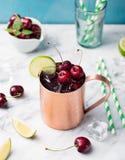Koude de Muilezelscocktail van kersenmoskou met gemberbier, wodka, kalk Marmeren achtergrondexemplaarruimte Stock Foto's