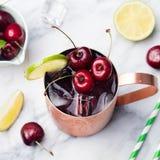 Koude de Muilezelscocktail van kersenmoskou met gemberbier, wodka, kalk Marmeren Hoogste mening als achtergrond Stock Fotografie