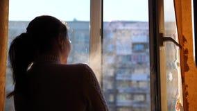 Koude de winterdag Het meisje opent het venster en ademt in de ijzige lucht stock videobeelden