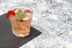 Koude de zomerdrank met munt en aardbei op een grijze achtergrond, exemplaarruimte stock foto's