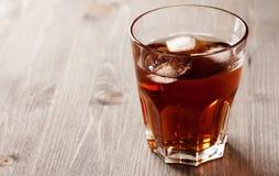 Koude drank met ijs in glas op houten lijst Stock Fotografie