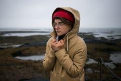 Koude en shievering jonge vrouw in regenjas royalty-vrije stock afbeeldingen