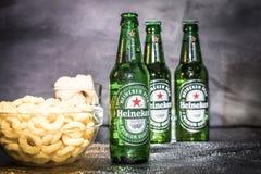Koude het bierflessen van Heineken met snacks op de achtergrond royalty-vrije stock afbeelding