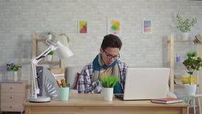 Koude jonge Aziatische mens in een overhemd met keelpijnzitting bij laptop stock videobeelden