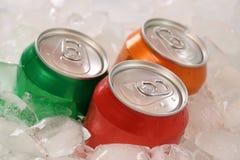 Koude kola en limonade in blikken op ijsblokjes Stock Fotografie
