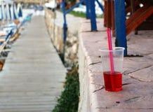 Koude rode drank met stro bij het strand Royalty-vrije Stock Afbeeldingen