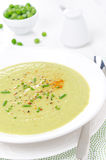 Koude soep van groene erwten met yoghurt, bieslookuien en peper Stock Afbeeldingen