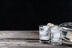 Koude wodka in geschotene glazen op een zwarte achtergrond Stock Foto's