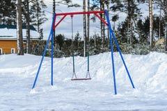 koude, zonder kinderen koude Speelplaats met eenzame bevindende schommeling op een ketting de sneeuw en de leegte stock foto