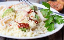 Kouskous met zeevruchten, droge tomaten, avocado en weinig toost Stock Afbeeldingen
