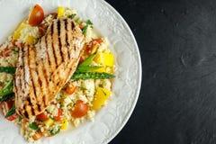 Kouskoussalade met geroosterde kip en asperge op witte plaat Steenlijst Gezond voedsel Stock Foto's