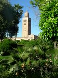 The Koutoubia mosque of Marrakech through the green vegetation of the public park, Marocco stock photography
