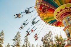Kouvola, Финляндия - 18-ое мая 2019: Carousel качания езды в движении в парке атракционов Tykkimaki и след воздушных судн в небе стоковые фотографии rf