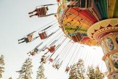 Kouvola, Финляндия - 18-ое мая 2019: Carousel качания езды в движении в парке атракционов Tykkimaki и след воздушных судн в небе стоковая фотография