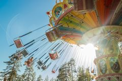 Kouvola, Finland - 18 May 2019: Ride Swing Carousel in motion in amusement park Tykkimaki and aircraft trail in sky stock images