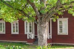 KOUVOLA, FINLANDIA - 20 DE SEPTIEMBRE DE 2018: Casa de madera vieja roja hermosa y árbol grande en el territorio del señorío de A imagenes de archivo