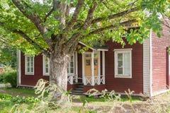 KOUVOLA, FINLANDIA - 20 DE SEPTIEMBRE DE 2018: Casa de madera vieja roja hermosa y árbol grande en el territorio del señorío de A fotos de archivo
