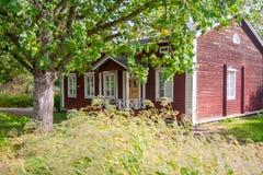KOUVOLA, FINLANDIA - 20 DE SEPTIEMBRE DE 2018: Casa de madera vieja roja hermosa y árbol grande en el territorio del señorío de A foto de archivo