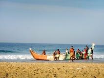 Fishermen are pulling out fishing boat at Kovalam. KOVALAM, INDIA - DEC 19: Kovalam, Kerala, South India, DEC 19, 2011. Unidentified local fishermen at Kovalam Stock Photo