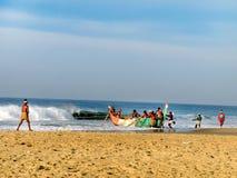 Fishermen are pulling out fishing boat at Kovalam. KOVALAM, INDIA - DEC 19: Kovalam, Kerala, South India, DEC 19, 2011. Unidentified local fishermen at Kovalam Stock Photography