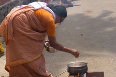 KOVALAM, KERALA, INDIA, April 1, 2015: Some women devotees participate in Pongala ceremony where boiled rice made in. Clay pots is offered to the god stock photo