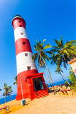 Kovalam Lighthouse Close People Angled. Kovalam, India - March 1, 2015: Closeup of red and white striped lighthouse surrounded by palm trees at Kovalem Beach in stock photos