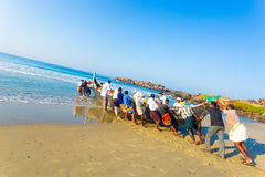 Kovalam Villagers Pushing Fishing Boat Sand Ocean. Community helping effort of villagers pushing fishing boat together from sand beach into water on a sunny royalty free stock photo