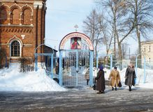 Kovrov,Russia-March 24,2012: Elderly woman is prayed beside entry in Cathedral. Kovrov,Russia-March 24,2012: Elderly woman is prayed beside entry in rescue Royalty Free Stock Photography