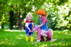 Kowbojów dzieciaki bawić się z zabawkarskim koniem Zdjęcie Stock