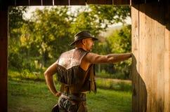 Kowbojów stojaki przy stajnią Przystojny mężczyzna z kapeluszem Obraz Stock