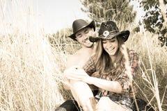 Kowboj i cowgirl dobieramy się obsiadanie w trawie, śmia się gdy łaskoczą each inny zdjęcie stock