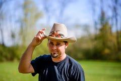 Kowboj w Śródpolny przechylanie kapeluszu ono Uśmiecha się szeroko Zdjęcia Royalty Free