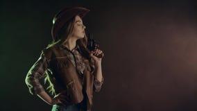 Kowbojska dziewczyna jest celująca strzał i robić Czarny dymny tło swobodny ruch zbiory