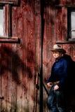 Kowbojski Opierać na stajni Patrzeje w słońce Zdjęcia Stock