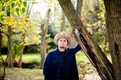 Kowbojski ranczer w lesie przy drzewem Fotografia Stock