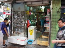 A man looks at different fish that are offered for sale in a shop located in Tung Choi stock photography
