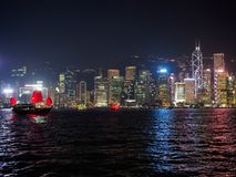 Hong Kong skyline at evening with a junk boat in the foreground. Kowloon, Hong Kong - November 2, 2017: Hong Kong skyline at evening with a junk boat in the royalty free stock image