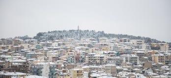 Kozani, Griechenland Traditionelle schneebedeckte Stadt und nebelhafter Himmelhintergrund Panoramische Ansicht Lizenzfreie Stockfotografie