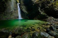 Kozjak vattenfall, Kobarid, Julian Alps, Slovenien i Europa Grön sjöyttersida vaggar in klyftan, stora våta stenar i förgrunden W royaltyfria bilder