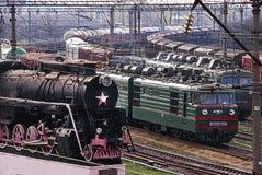Kozyatyn, Ukraine - 10. April 2010: Alter historischer Dampfzug und neue Güterzüge Stockbilder