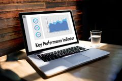 KPI acronym (Key Performance Indicator) Business team hands at w. Ork with financial reports and a laptop Royalty Free Stock Images
