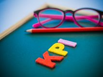 Woking office concept. KPI alphabet with red pencil and pink glasses put on blackboard Stock Images