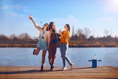 Krótkopęd trzy pięknej dziewczyny outdoors rzeką Żeńscy przyjaciele relaksuje ono uśmiecha się i rzeką Dziewczyny są statywowe zdjęcie royalty free