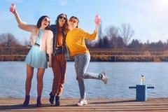 Krótkopęd trzy pięknej dziewczyny outdoors rzeką Żeńscy przyjaciele relaksuje ono uśmiecha się i rzeką Dziewczyny są statywowe zdjęcie stock