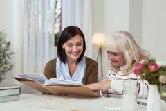 Kräftige ältere Frau und Pflegekraft betreffend Fotoalbum lizenzfreie stockfotografie