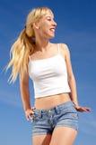 Kräftige junge blonde Frau auf Hintergrund des Himmels Lizenzfreie Stockbilder