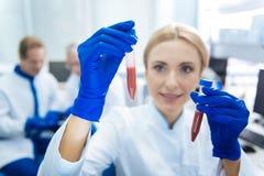 Kräftiger Wissenschaftler, der Blutproberohre hält Lizenzfreies Stockfoto